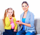 Mom gives girl red apples — Stock Photo