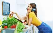 烹饪与耳机的女人 — 图库照片
