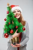 Woman holds Christmas tree — Stok fotoğraf