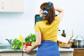 Woman cooking with headphones — Photo