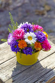Chrysanthemum bouquet in a basket  on old wooden stool — Stock Photo