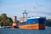 Cargo ship with tug boat — Stock Photo