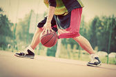 Man on basketball court dribbling with ball. — Stock Photo