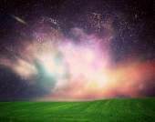 Field of grass under galaxy sky — Stock Photo