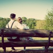 Young couple in love sitting on a bench — Stock Photo #77544006