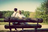 Young couple in love sitting on a bench — Stock Photo