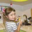 Little girl in kitchen washes the dishes — Stock Photo #59038769