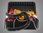 Black basket with christmas decorations isolated on gray backgro — Stock Photo