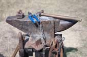 Old anvil with many blacksmith tools — Stock Photo