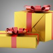 Two yellow gift boxes with red ribbons isolated on gray backgrou — Stock Photo #57512761