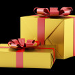 Two yellow gift boxes with red ribbons isolated on black backgro — Stock Photo #59797121
