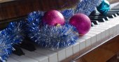 Attributes of celebration of New year and Christmas lie on a piano — Stock Photo