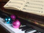 Attributes of celebration of New year and Christmas lie on a piano — Foto de Stock