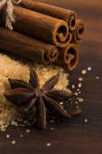 Cinnamon sticks with pure cane brown sugar on wood background — Stock Photo