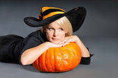 Pretty blonde woman in a costume of witch posing with pumpkins — Stock Photo