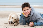 Boy and retriver on the beach — Stock Photo