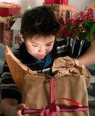 Boy unpacks a gift — Stock Photo