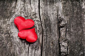 Two satin red hearts on wooden background — Stock Photo
