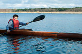 The boy rowing in a kayak on the river — Stock Photo