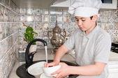 Boy washing dishes — Stock Photo