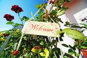 Welcome sign hanging on flowers — Stock Photo