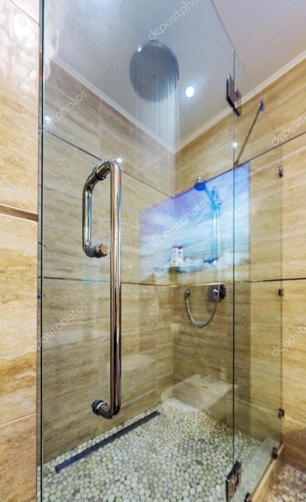 en witte badkamer met witte tub, beige tegel vloer, glazen deur douche ...