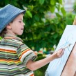 Little boy draws a picture outdoor — Stock Photo #74203413