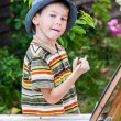 Little boy draws a picture outdoor — Stock Photo #74203445