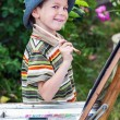 Little boy draws a picture outdoor — Stock Photo #74203495