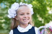 Joyful girl first grader with flowers — Stock Photo