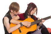 Boy teaches girl to play the guitar — Stockfoto