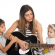 Mother playing guitar for their children — Stock Photo #54661161