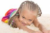 Cute little girl with dreadlocks lays  — Stock Photo