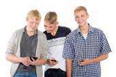 Three young guys use smartphones — Foto Stock