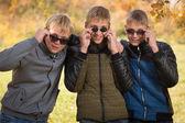 Three guys in sunglasses in autumn park — Stock Photo
