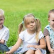 Smiling children are resting on the lawn — Stock Photo #62336607