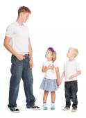 Younger brother and sister look at older brother — Stock Photo