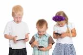 Little brothers and sister using smartphones — Stock Photo
