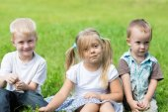 笑顔の子供たちが芝生の上に休んでいます。 — ストック写真