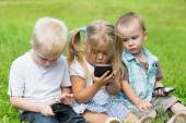 Kids playing on smartphones sitting on the grass  — Stock Photo