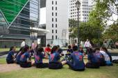 Boys and girls sitting in downtown Singapore — Stock Photo