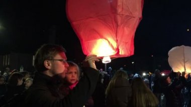 Father and daughter releasing paper lantern at night — Stock Video