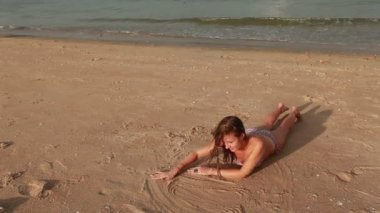 Woman on the beach drawing on sand — Stock Video