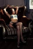 Brunette wearing black lingerie posing on chair — Stock Photo