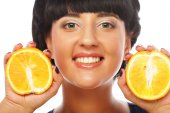 Happy girl holding oranges over face — Stock Photo