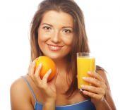 Young happy woman drinking orange juice — Stock Photo