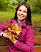 Young elegant woman with autumn leaves — Stock Photo