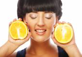 Happy girl holding oranges over face — 图库照片