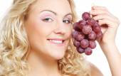 Young woman  holding bunch of grapes — Stock Photo