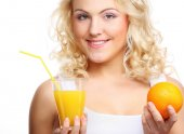 Young happy woman drinking orange juice. — Stock Photo
